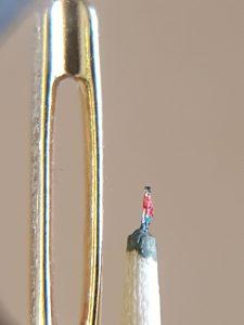 Schlanker Mann neben Nadelöhr. Der Mann ist ca. 1 mm hoch, hat schwarze Haare, trägt ein rotes Hemd und blaue Hose