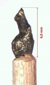 Bronzene Figur wie ein sitzender Bär nach links blickend. Mikrofigur mit 4 Millimetern Größe.