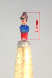 Frau mit Sonnenbrille, rotes Kleid, blaues Oberteil, braune Haare. Zwei Millimeter groß.