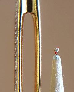 Weißer Hahn neben Nadelöhr
